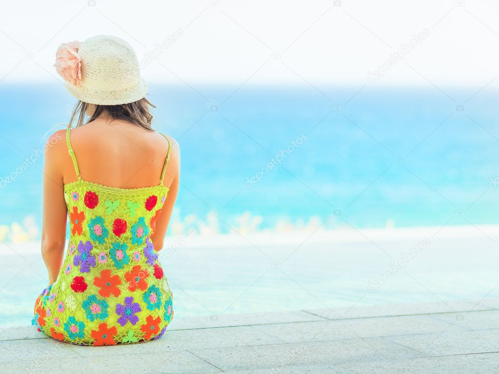 Rear view of woman sitting on the edge of swiming pool — Stock Photo #10345098