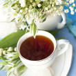 Tea in a cup and lilies of the valley — Stock Photo #8644375