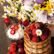 Stock Photo: Strawberries and bouquet of flowers
