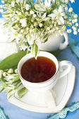 Tea in a cup and lilies of the valley — Stock Photo