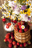 Strawberries and bouquet of flowers — Stock Photo