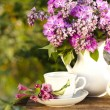 Porcelain cup with coffee and lilac — Stock Photo