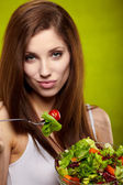 Female of cute appearance eats vegetable vegetarian salad — Stock Photo