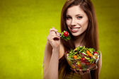 The beautiful cheerful young woman has breakfast salad — Stock Photo