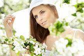 Portrait of young lovely woman in spring flowers — Stock Photo