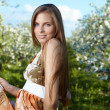 Portrait of young lovely woman in spring flowers over amazing ga — Foto Stock