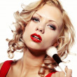 Beautiful blond woman applying makeup on her face — Stock Photo #10566131