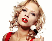 Beautiful blond woman applying makeup on her face — Stock Photo