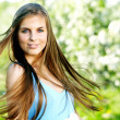 Beautiful woman wearing blue dress over spring orchard — Stock Photo #10661555