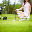 A pretty woman golfer on the putting green — Stock Photo