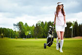 A pretty woman golfer on the putting green — Stok fotoğraf