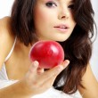 Stock Photo: Portrait of woman sitting on bed and eating fresh red apple