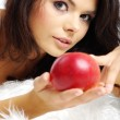 Portrait of woman sitting on bed and eating fresh red apple — Stock Photo