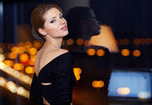 Young ellegant woman standing on the ligths of the night city ba — Stock Photo