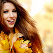 Young woman in autumn orange leaves. Outdoor. - 图库照片