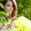 Happy smiling young woman with flower bouquet over yellow green - Stock Photo