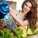 Cheerful girl watering flowers — Stock Photo #8725473