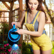 Cheerful girl watering flowers — Stock Photo