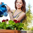 Cheerful girl watering flowers — Stock Photo #8725638