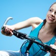 Woman with bike under blue skies - Stock Photo