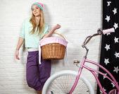 自宅でショッピング前にピンクのバイクを持つ若い女 — ストック写真