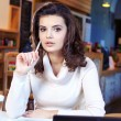 A young attractive business woman sitting in a cafe with a lapto — Stock Photo