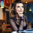 Stock Photo: Charming sexy woman in black clothes sits at magnificent cafe