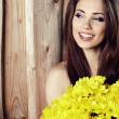 Closeup portrait of cute young girl with yellow flowers smiling — Stock Photo