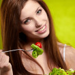 Happy healthy woman with salad on green background — Stock Photo