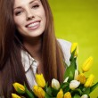 Smiling girl with yellow tulips. green background — Stock Photo #9389176