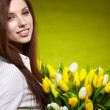Stock Photo: Smiling girl with yellow tulips. green background