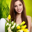 Portrait of a girl with white and yellow tulips - Stock Photo