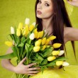 Young woman hold yellow tulips flower on green — Stock Photo #9389379