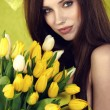 Young woman hold yellow tulips flower on green — Stock Photo