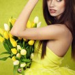 Young woman hold yellow tulips flower on green — Stock Photo #9389500