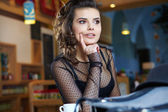 Young woman sitting in the cafe with a cup of tea — Stock Photo