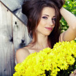 Young happy girl in yellow flowers, outdoor photo session - Stock Photo