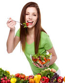 Portrait of a pretty young woman eating vegetable salad against — Stock Photo