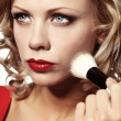 Beautiful blond woman applying makeup on her face — Stock Photo #9774962