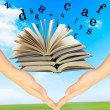 Magic Book and the letters over hands — Stock Photo #8127579