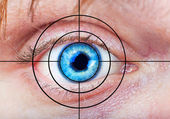 Man's blue eye and target — Stock Photo