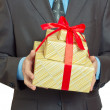 Businessman present gift box with red ribbon bow — Stock Photo