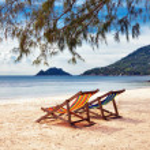 Two sun beach chairs on shore near sea — Stock Photo #8302099