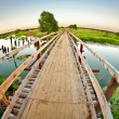 Wooden bridge over the small river — Stock Photo