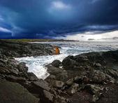 Volcanic stonesl beach under gloomy sky — Stock Photo
