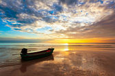 Boat on the beach at sunset — Stock Photo