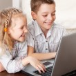 Happy kids playing laptop at home — Stock Photo #10029786