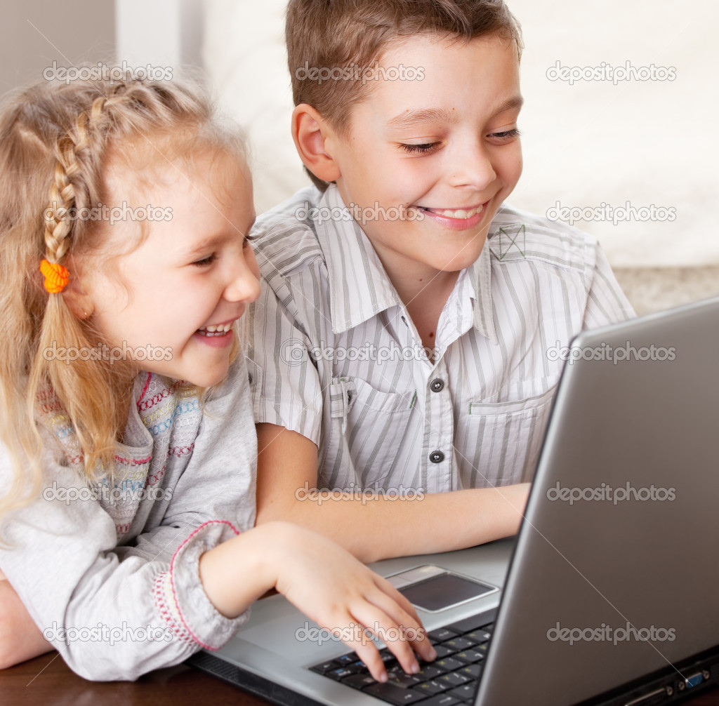Children with laptop indoors. Happy kids playing computer at home.  Stock Photo #10029786