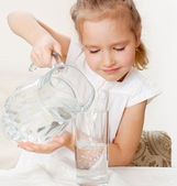 Child with glass pitcher water — Stock Photo