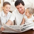 Family reading a newspaper — Stock Photo